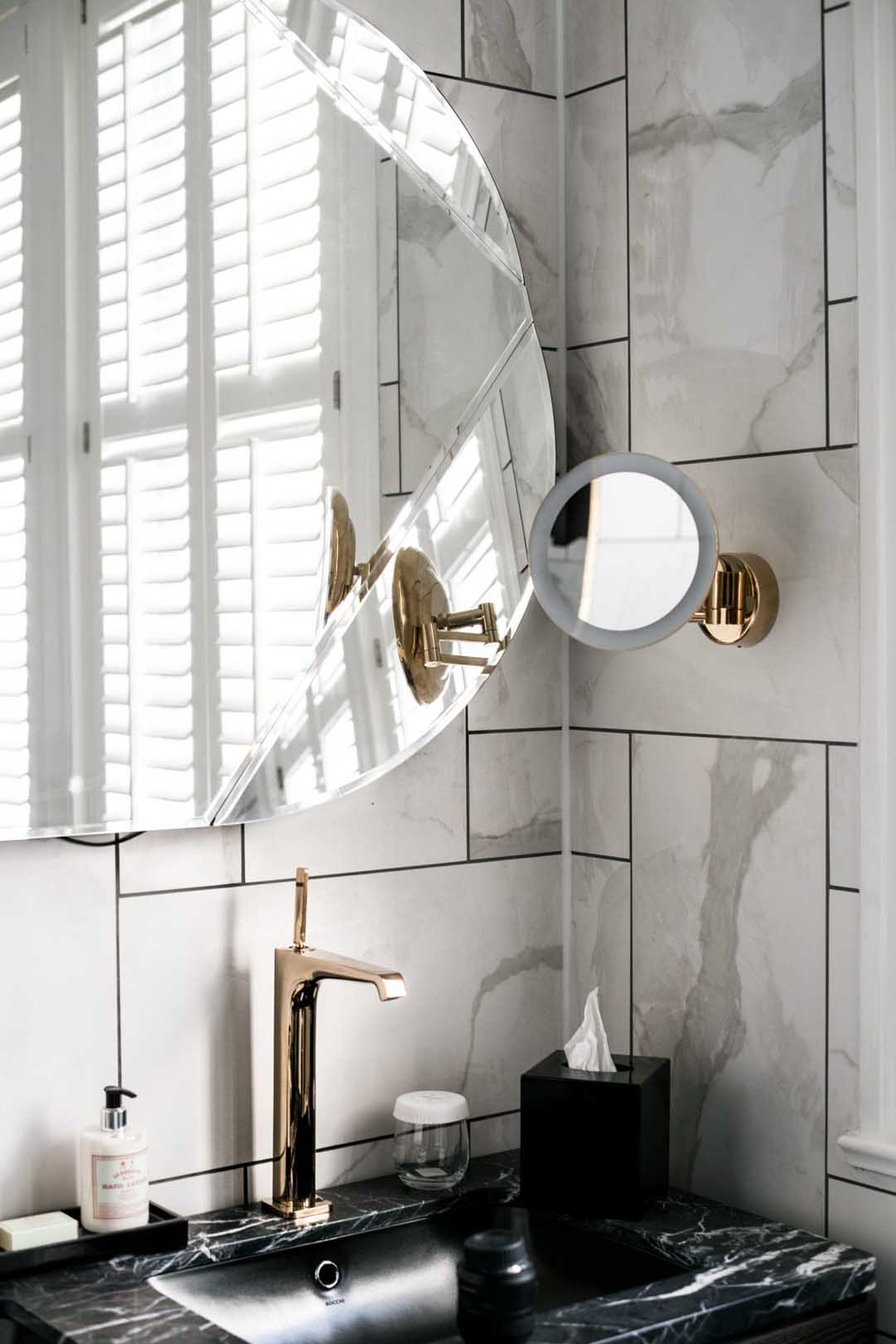 Image of the bathroom sink with brass taps and a circular mirror on the wall