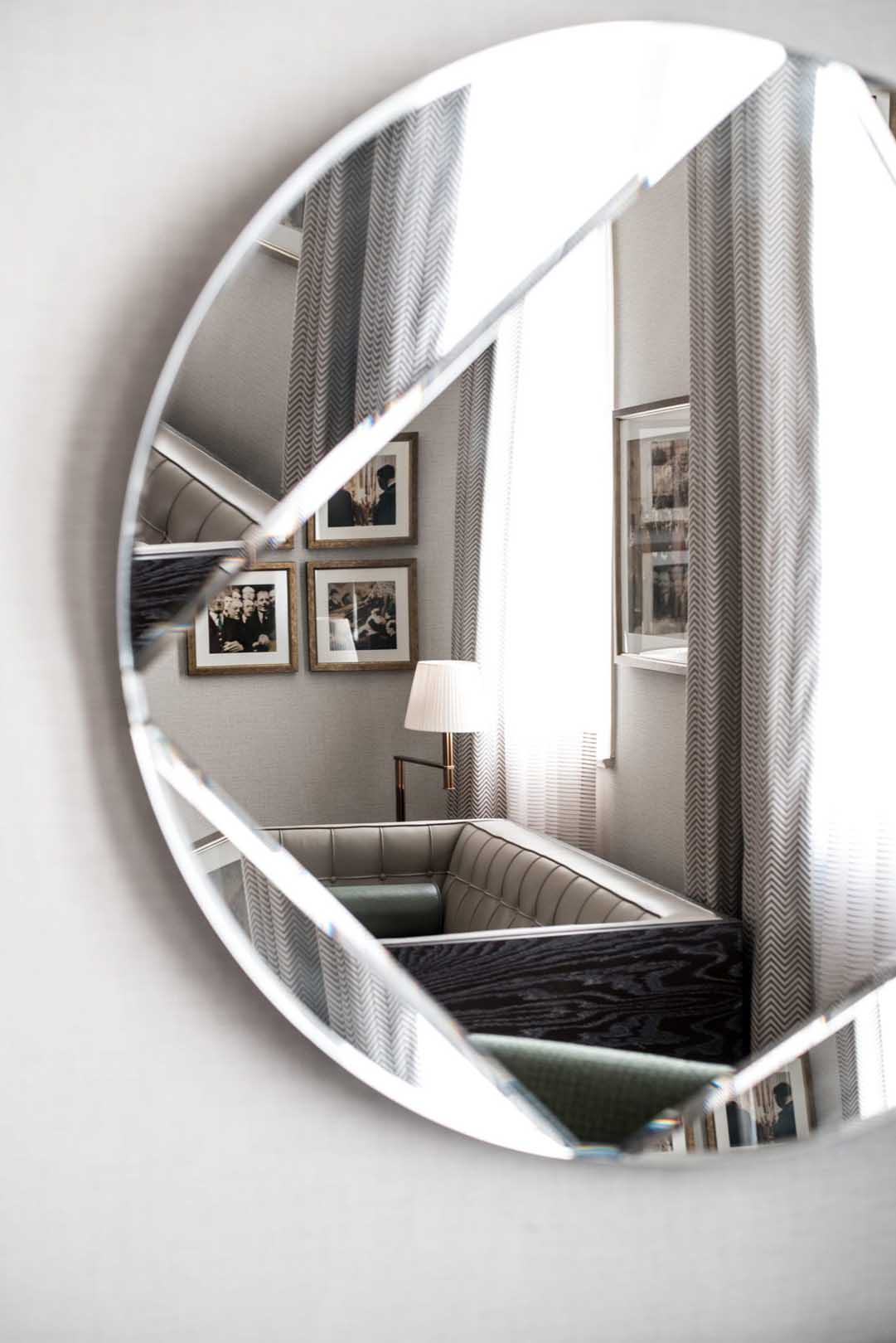 Circular mirror in a bedroom