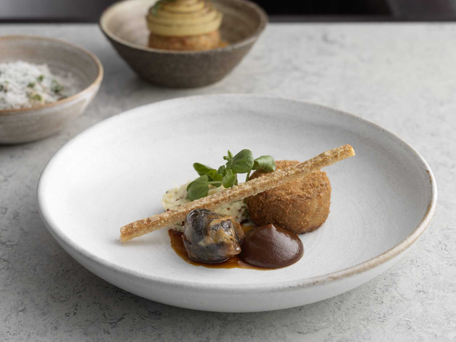 Crispy pigs head with crackling, mustard mash and a rich sauce