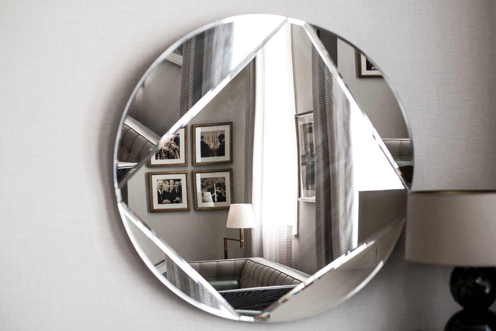 Circular mirror with a reflection of pictures hung on the wall
