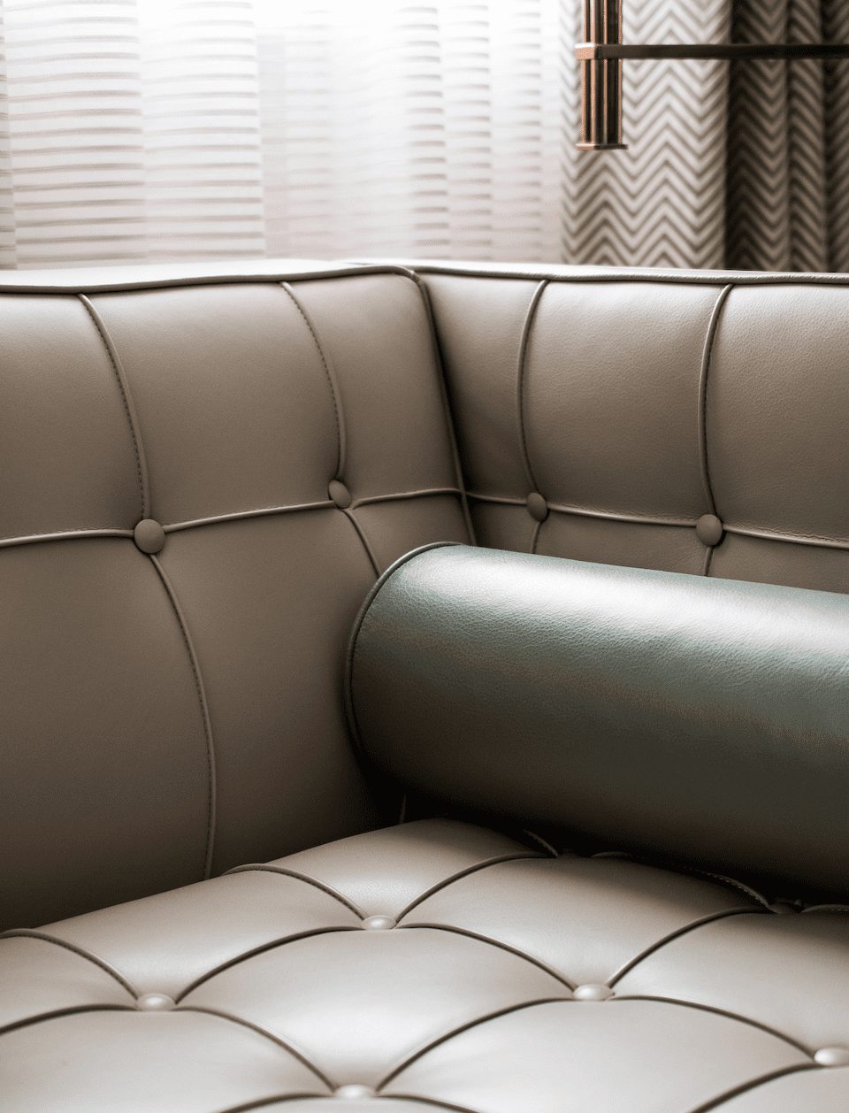 Corner of a leather sofa with cushions
